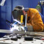 Man welding metal in a work environment