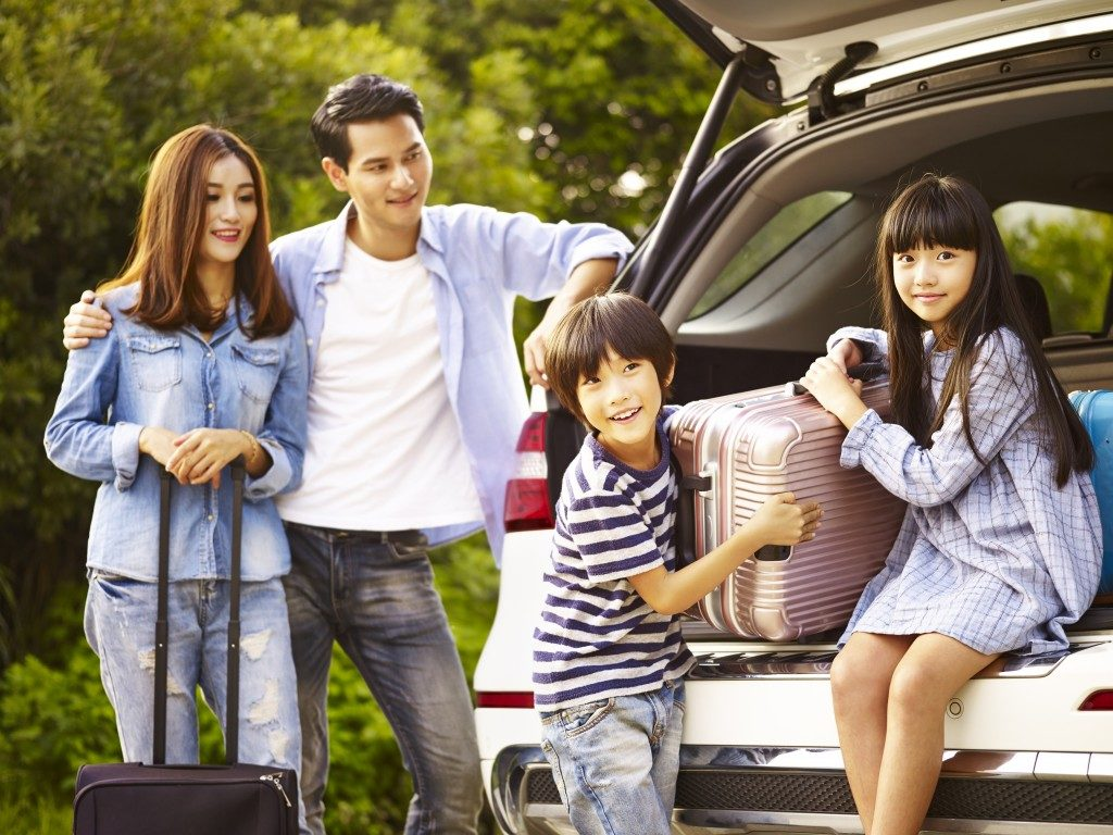 Family unloading luggage from SUV