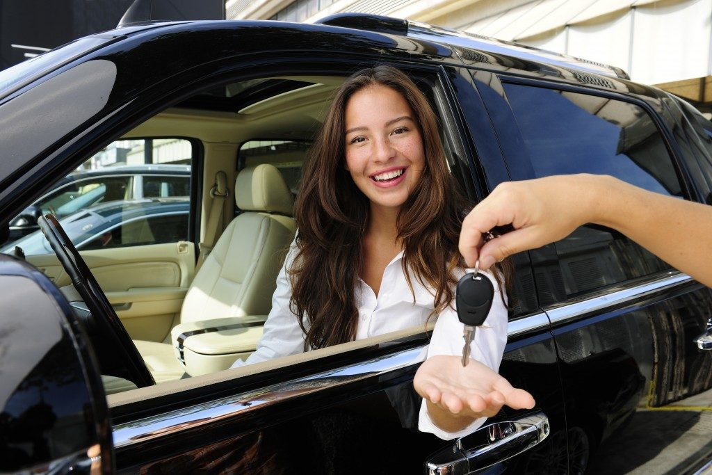 woman smiling while getting the key for her SUV