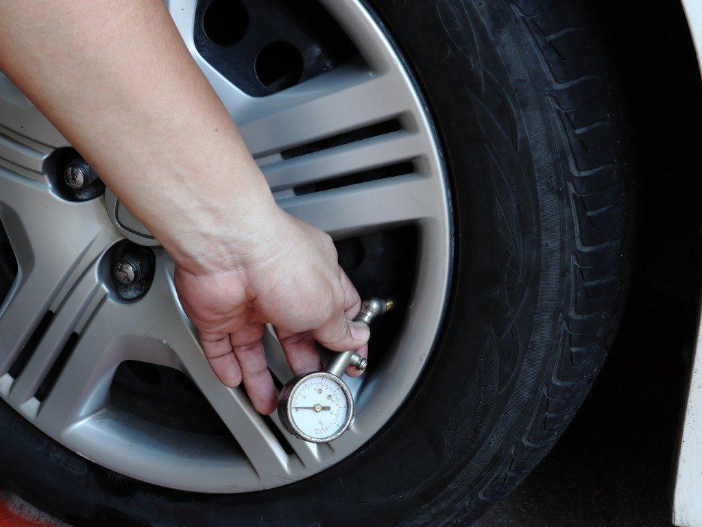 person checking the tire pressure