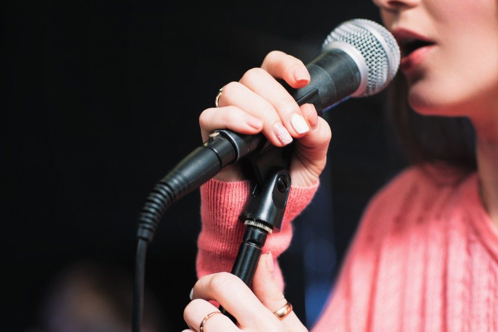 Microphone and unrecognizable female singer close up