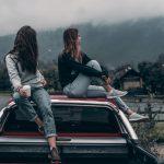 women sitting on a truck